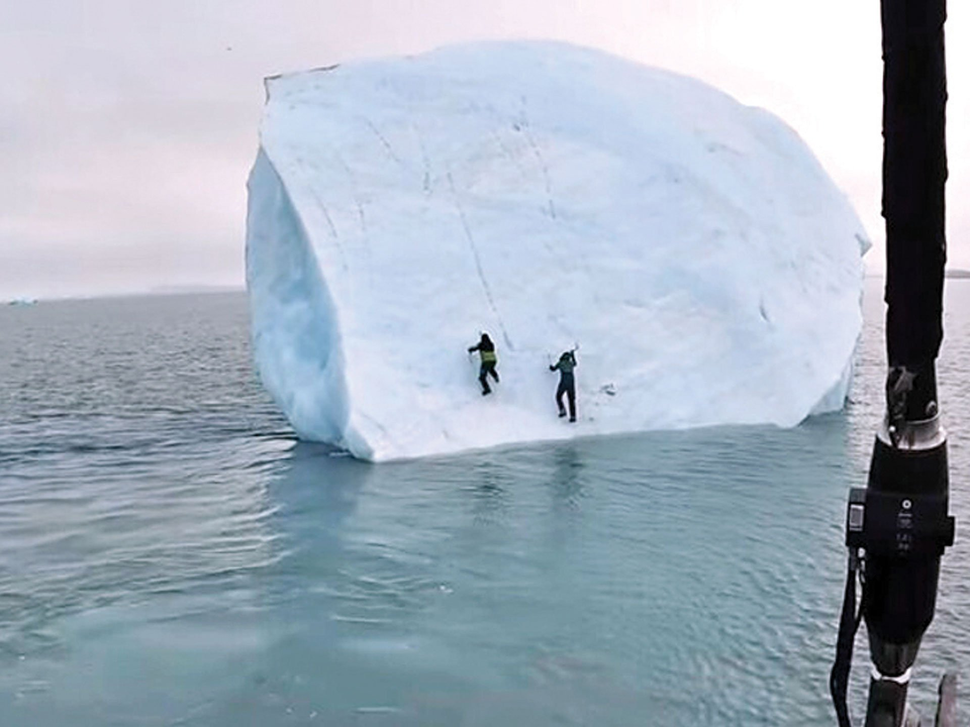 An iceberg turns over on two adventurers in the Arctic Ocean