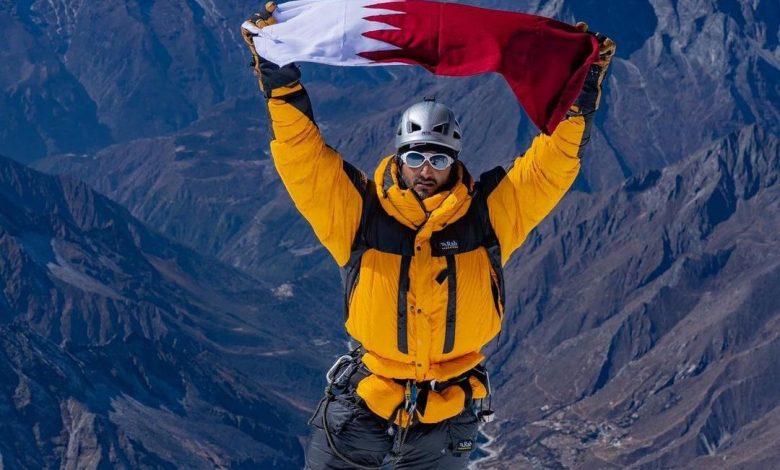 The Qatari flag flies over the summit of Ama Dablam